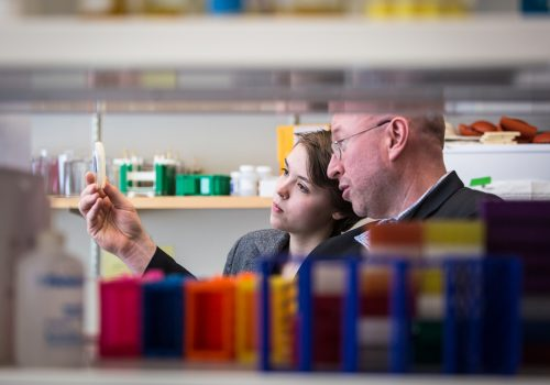 Ted Meigs looking at a culture in the lab with a student